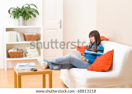 Teenager girl relax home - sitting on sofa with touch screen tablet computer