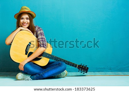 Teenager girl seating on a floor with acoustic guitar. - stock photo