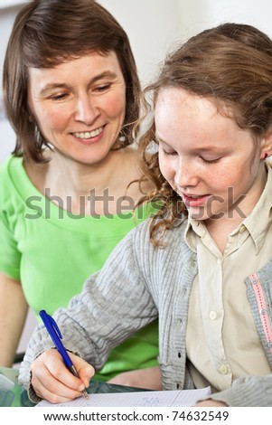Teenager girl sitting together with her mother and showing her homework - stock photo