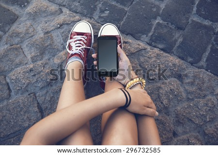 teenager girl sitting with mobile phone in hand, in ancient stone floor - stock photo