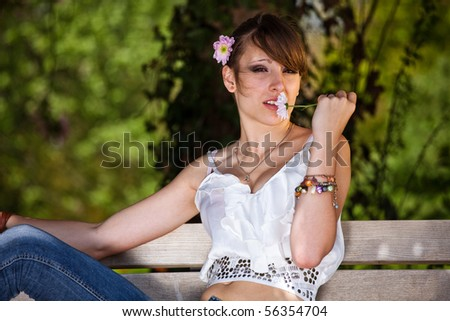 Teenager girl smelling flower outside during a summer day in the park. - stock photo