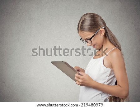 Teenager girl using pad computer playing game isolated grey wall background. Next generation technology concept. Student education. Positive human face expression emotion. Modern source information - stock photo