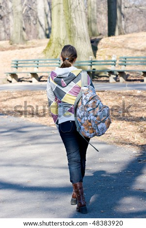 Teenager girl walking on a street with a book bag after school - stock photo