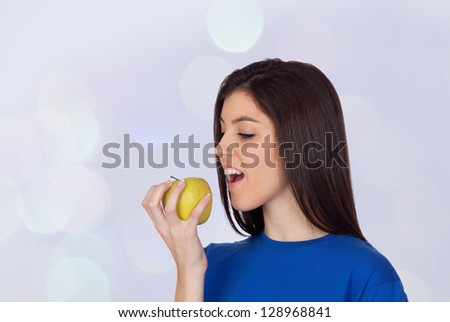 Teenager girl with a yellow apple isolated on blue background - stock photo