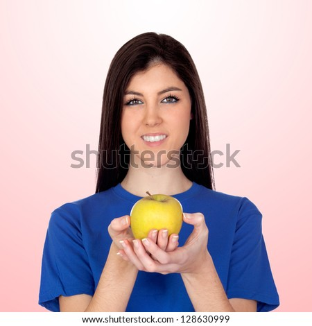 Teenager girl with a yellow apple isolated on pink background - stock photo