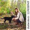 Teenager girl with black labrador retriever puppy outdoors - stock photo