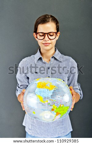 Teenager girl with blue shirt with globe ball on black background
