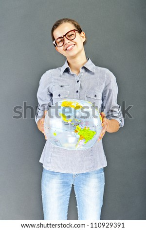 Teenager girl with blue shirt with globe ball on black background - stock photo