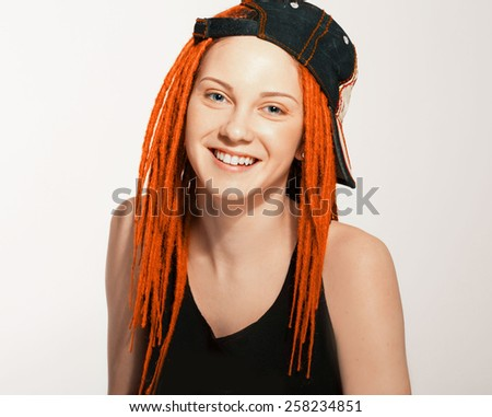 Teenager girl with dreadlocks red hair and cap smiling studio portrait - stock photo