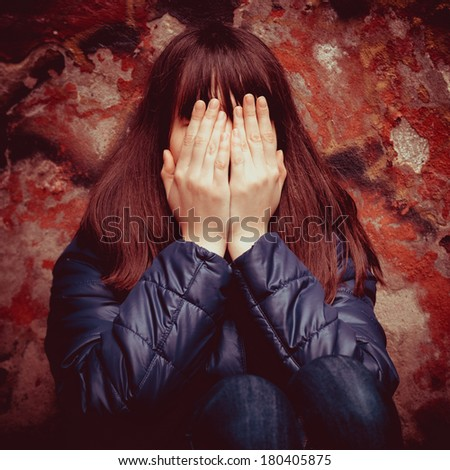 teenager girl with hands over eyes near dramatic red wall outdoors - stock photo