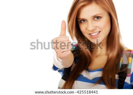 Teenager girl with school backpack and thumb up - stock photo