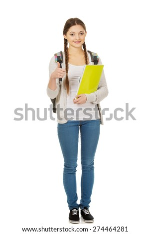 Teenager girl with school backpack and thumbs up. - stock photo
