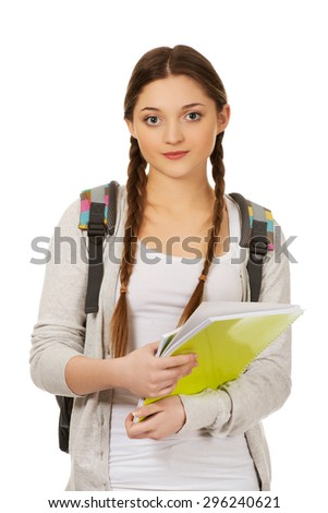 Teenager girl with school backpack holding folder.