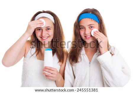 Teenager girls cleaning theirs face with tonic lotion - stock photo