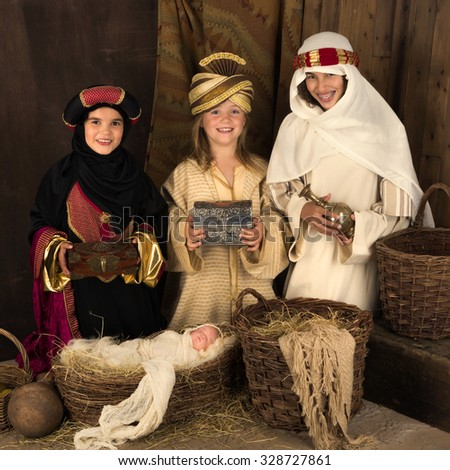 Teenager girls playing a live Christmas nativity scene (the baby is a doll) - stock photo