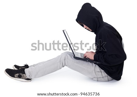Teenager hacker with black hood and laptop