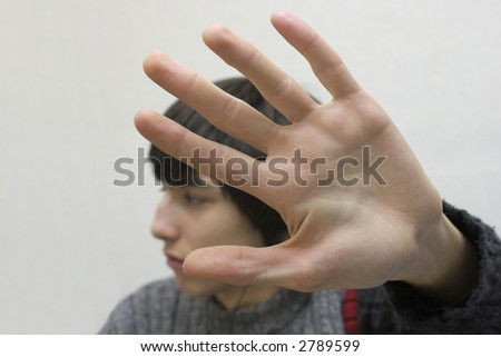 Teenager hides his face by hand. - stock photo
