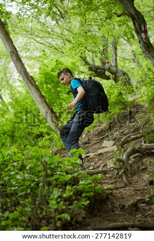 Teenager hiker boy with backpack on a trail in the mountains - stock photo