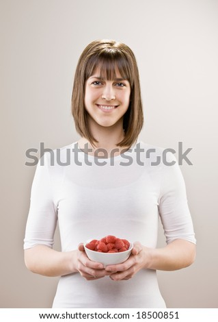 Teenager holding bowl of wholesome, fresh raspberries