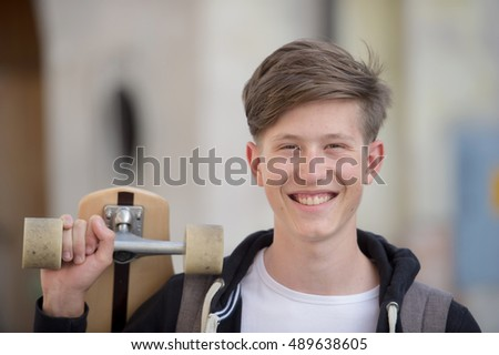 Teenager holding longboard and smiling.