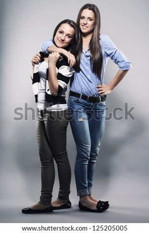 teenager hugging her sister on gray background - stock photo