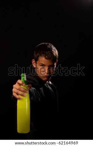 Teenager impersonating James Bond holding a cleaning spray - stock photo
