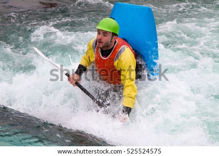 Teenager in a kayak bobbing vertically in fast flowing water about to do a roll