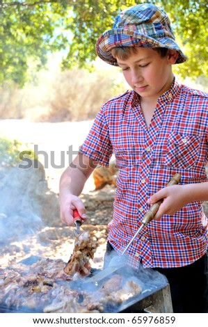 teenager in a park on a holiday to cook meat and steaks on the grill