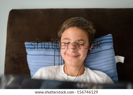Teenager in bed with laptop - stock photo