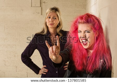 Teenager in pink hair with disapproving mother in background