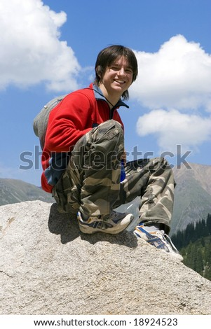 Teenager in red sport pullover against blue sky in mountain hike, Tien Shan - stock photo