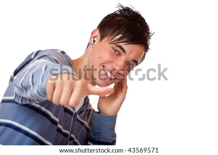Teenager is listening to mp3 music with earphones and shows thumb up. Isolated on white.