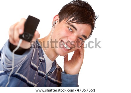 Teenager is listening to music with earphones and holding his mp3 player into camera. Focus on teenager. Isolated on white.