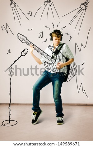 teenager is playing on drawn guitar at concert - stock photo
