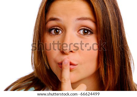 Teenager isolated in studio puts her finger to her lips - stock photo