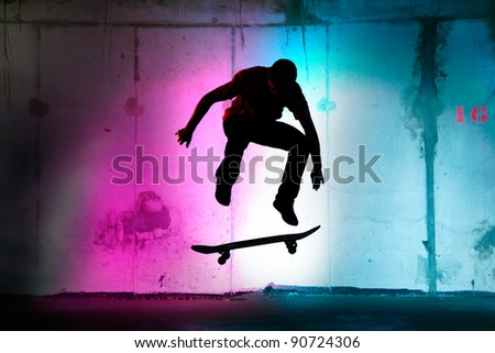 teenager jumping, skateboarding at night black silhouette - stock photo
