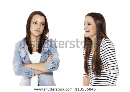 teenager laughing at her upset sister on white background - stock photo
