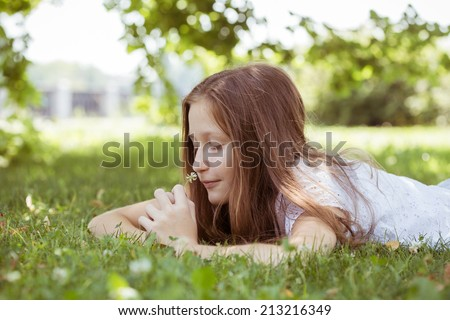 teenager lies on a grass at the park