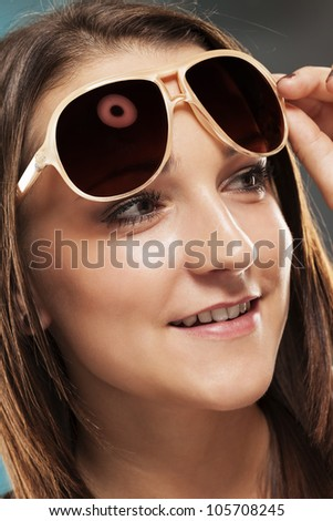 teenager lifting her sunglasses looking to side - stock photo