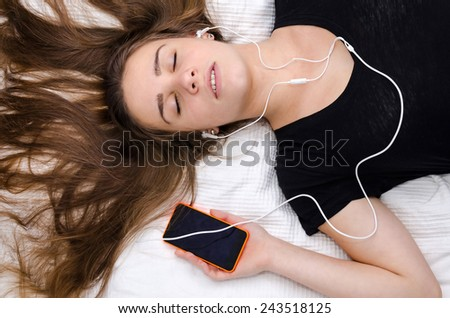 Teenager listening music on the bed - stock photo