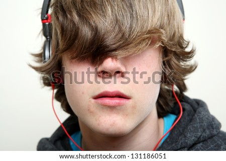 Teenager listening to music, hiding behind his hair - stock photo