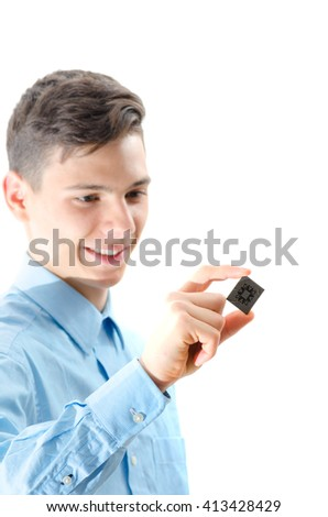 Teenager looking at a micro chip isolated on white background - stock photo