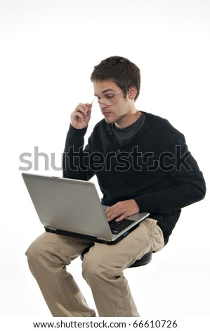 teenager looking at laptop holding onto glasses - stock photo