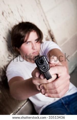 teenager male aiming modern handgun gun at camera - stock photo