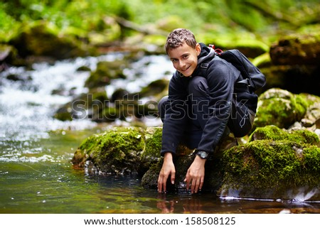 Teenager near the river - stock photo