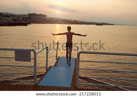 Teenager on a background of the rising sun prepares to jump into the sea. Early morning. Antalya. Turkey. - stock photo