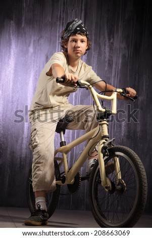 teenager on a bicycle on a background of industrial landscape - stock photo
