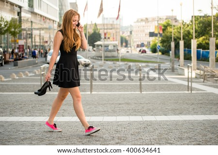 Teenager on the phone walking down street in sneakers and high heels shoes holding in hands