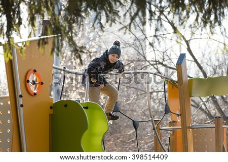 Teenager on the playground on a sunny day in early spring