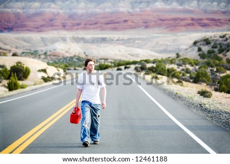 teenager out of gas, walking down rural mountain road with gas can - stock photo